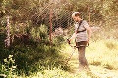 Ein Mann mäht das Gras in seinem Garten mit einem Trimmer stockbild