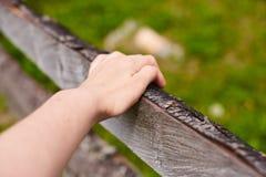 Ein Mann möchte über einen Zaun auf dem Gebiet springen Nahaufnahmeansicht der Hand Stockbild
