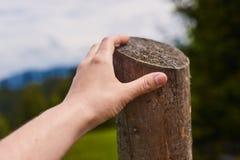 Ein Mann möchte über einen Zaun auf dem Gebiet springen Nahaufnahmeansicht der Hand Lizenzfreie Stockfotos