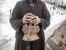 Ein Mann mit dem Feuertopf, zum seiner Hände zu warnen Stockbilder