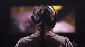 Ein Mann mit dem langen Haar, einen Film oder ein Clip aufpassend, tanzt er zum Schlag der Musik 4K langsames MO stock video
