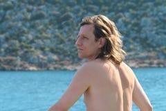 Ein Mann mit dem langen Haar hat seine Rückseite auf dem Meer gedreht