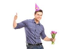 Ein Mann mit dem Partyhut, der einen Blumenstrauß anhält Stockbilder