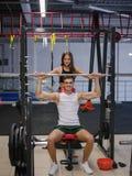 Ein Mann mit dem schönen athletischen Körper, der Übungen mit einem Barbell auf einem Turnhallenhintergrund tut Eignung, bodybuil lizenzfreies stockfoto