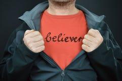 Ein Mann mit dem Wortgläubiger auf seinem roten T-Shirt lizenzfreies stockbild