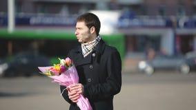 Ein Mann mit den Blumen, die auf seine Frau in der Stadt warten stock video