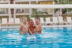 Ein Mann mit den Kindern, die Spaß im Pool im Freien haben lizenzfreies stockbild