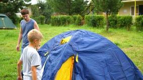 Ein Mann mit den Kindern, die Zelt erfassen stock footage