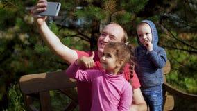 Ein Mann mit den Kindern fotografiert auf einem Smartphone, der auf einer Bank sitzt Glückliche Familie, die selfie im Park nimmt stock video footage