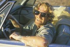 Ein Mann mit der Sonnenbrille, die ein Cadillac-Kabriolett fährt Lizenzfreie Stockfotos