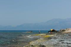 Ein Mann mit einem Angelrutenfischen auf dem Ufer von t Lizenzfreie Stockfotos