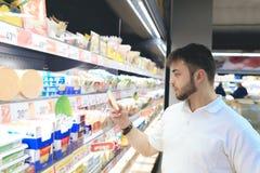 Ein Mann mit einem Bart kauft Lebensmittel in einem Supermarkt Ein junger Mann wählt Milchprodukte auf den Regalen des Supermarkt Lizenzfreie Stockbilder