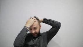 Ein Mann mit einem Bart macht das Haaranreden stock footage