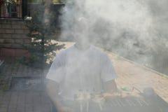 Ein Mann mit einem Bart nahe dem Feuer und der Grill braten Fleisch und Würste Stockbilder