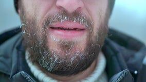 Ein Mann mit einem Bart und Glasblicke in die Kamera Er ist die Außenseite, sehr kalt stock footage