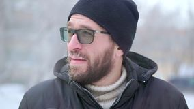 Ein Mann mit einem Bart und Glasblicke in die Kamera Er ist die Außenseite, sehr kalt stock video