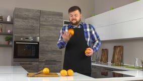 Ein Mann mit einem Bart und einem Schutzblech wirft eine Orange in der modernen Küche, eine gesunde Diät, Zeitlupe stock video footage