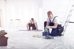 Ein Mann mit einem Berufswerkzeuggurt, der eine Dose der grünen Wand hält stockbilder