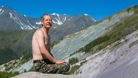 Ein Mann mit einem bloßen Torso in den Bergen Stockfotos