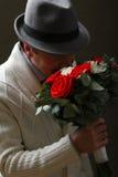 Ein Mann mit einem Blumenstrauß von Rosen Lizenzfreies Stockfoto