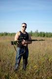 Ein Mann mit einem Gewehr in seinen Händen Lizenzfreie Stockbilder