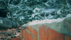 Ein Mann mit einem Jackhammer demoliert die Backsteinmauer des Hauses langsam stock video