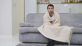 Ein Mann mit einem kalten Sitzen auf der Couch in einer Decke ist so kalt, wie möglich Kranker Mann des Mannes zu Hause - Graues  stock video