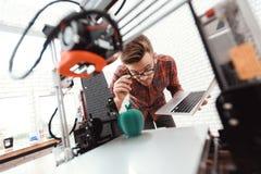 Ein Mann mit einem Laptop in seinen Händen steuert den Prozess des Druckes eines Druckers 3d Drucker 3d hat Modell eines Apfels g lizenzfreie stockfotografie