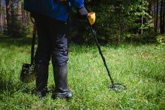 Ein Mann mit einem Metalldetektor im Wald stockbild