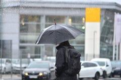 Ein Mann mit einem Regenschirm im Regen, der die Straße kreuzt stockbild