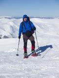 Ein Mann mit einem Rucksack und Schneeschuhen Lizenzfreie Stockbilder