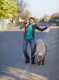 Ein Mann mit einem schmutzigen Schwein Stockbild