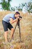 Ein Mann mit einem Stativ und einer Kamera, die auf einer Wiese stehen Lizenzfreies Stockfoto