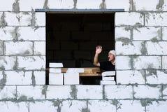 Ein Mann mit einem Verband auf seinem Kopf mit seiner Hand hob in ein Haus an Lizenzfreies Stockbild
