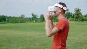Ein Mann mit einem VR-Kopfhörer auf seinem Kopf im Park betrachtete die Kamera und lächelte stock video footage