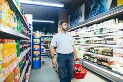 Ein Mann mit einem Warenkorb in seinen Händen geht zum Supermarkt und betrachtet die Seiten Der Käufer wählt die Produkte stockfotografie