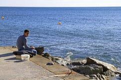 Ein Mann mit einer Angelrute auf einem Seeufer fängt Fische lizenzfreies stockfoto
