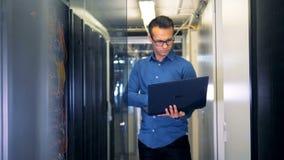 Ein Mann mit einer Laptopstellung in einem Serverraum stock video