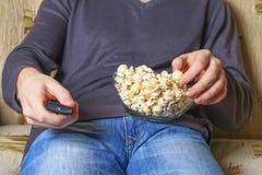 Ein Mann mit einer Schüssel Popcorn und einer Fernbedienung in seiner Hand betrachtet das Fernsehen auf dem Sofa Stockbilder