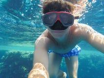 Ein Mann mit einer Unterwassermaske schwimmt nahe den Korallen im Meer Stockbilder