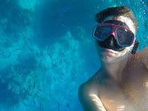 Ein Mann mit einer Unterwassermaske schwimmt nahe den Korallen im Meer Lizenzfreie Stockbilder