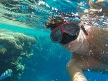 Ein Mann mit einer Unterwassermaske schwimmt nahe den Korallen im Meer Lizenzfreie Stockfotos