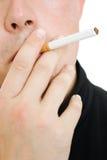 Ein Mann mit einer Zigarette in seinem Mund. lizenzfreie stockbilder