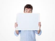 Ein Mann mit halber Gesichtsabdeckung durch ein leeres Brett aufpassendes somethin Lizenzfreies Stockbild