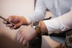 Ein Mann mit intelligentem Telefon in einer entspannten Haltung in einem weißen Hemd schreibt sms Psychologie und Verhandlungskon stockfotografie