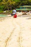 Ein Mann mit rotem Koffer verlässt sein Hotel, Philippinen, die Boracay ist Lizenzfreie Stockfotos