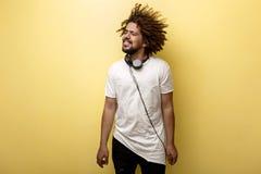Ein Mann mit seinem Haar in kräuseln sich und Kopfhörer auf dem Hals ist, schauend nett stehend und seitlich tragen asymetrisch stockbild