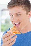 Ein Mann mit seinem Mund geöffnet ungefähr, zum der Pizza zu essen Lizenzfreie Stockfotografie