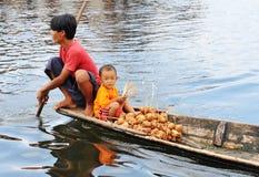 Ein Mann mit seinem Sohn auf dem Boot in der Einlegearbeit, Myanmar Lizenzfreie Stockbilder