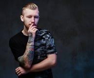 Ein Mann mit Tätowierungen auf Armen Lizenzfreies Stockbild